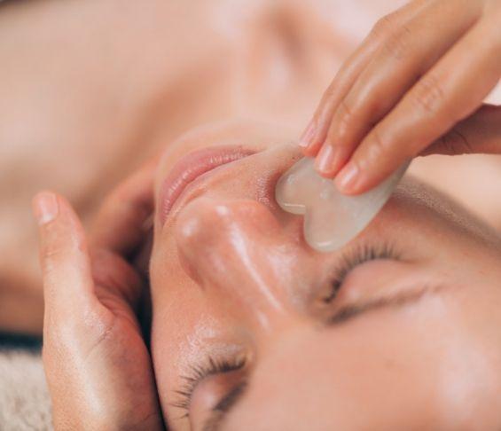 Kosmetologi tekee itämaista kasvohierontaa asiakkaalle.