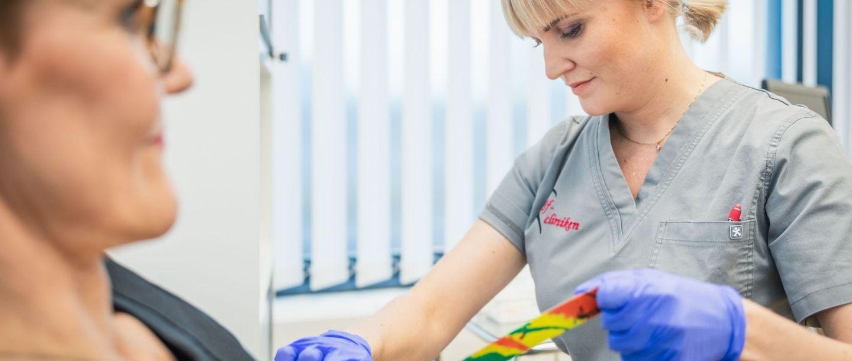 Synlab yhteistyössä Sf-clinikenin kanssa - sairaanhoitaja ottaa verikoetta.